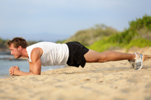 man performing plank on the beach