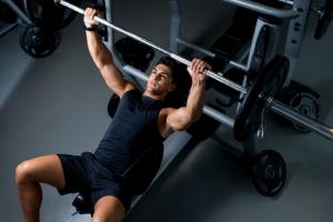 man bench pressing at Shape Up Fitness & Wellness Consulting with a personal trainer