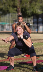 Middle aged woman squatting with kettlebell
