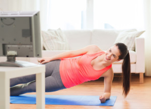 Young woman exercising at home doing side planks